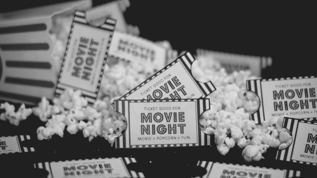 Movie tickets with popcorn around it.